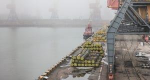 Panoramic  view of cargo port in fog. Tug, crane, dry cargo ship royalty free stock photos