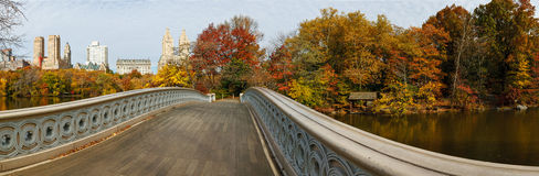 Panoramic view of Central Park autumn trees from B. Fall colors in Central Park, NYC. Horizontal panoramic photograph with Bow Bridge and the Lake in the Stock Photography