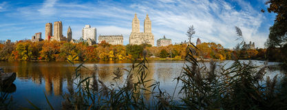 Panoramic view of Central Park Lake at fall. Urban view of Manhattan, New York, from the Lake in Central Park in autumn. The morning light enhances the colorful Royalty Free Stock Photography