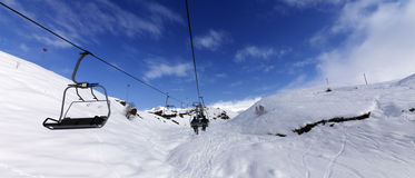 Panoramic view on chair-lift at ski resort at sun winter day Royalty Free Stock Photo