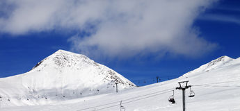 Panoramic view on chair-lift and ski slope at sun day Stock Photos