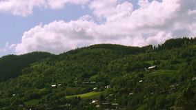 Panoramic view of city at mountains covered green woods in summer sunny day. Cloud drift. Nature.  stock video footage