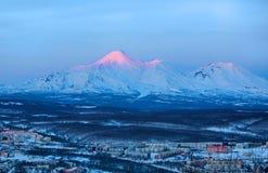 Panoramic view of the city Petropavlovsk-Kamchatsky and volcanoe. S: Koryaksky Volcano, Avacha Volcano, Kozelsky Volcano. Russian Far East, Kamchatka Peninsula Royalty Free Stock Images
