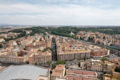 Panoramic view on city of Rome from Papal Basilica of St. Peter. (St. Peter's Basilica). Summer day, people walk on street and cars on road royalty free stock photo