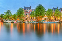 Panoramic view and cityscape of Amsterdam with boats, old buildings and Amstel river, Holland, Netherlands Royalty Free Stock Photos