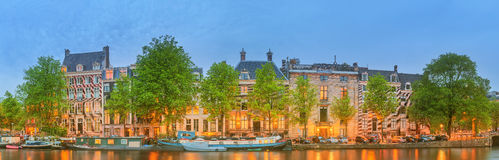 Panoramic view and cityscape of Amsterdam with boats, old buildings and Amstel river, Holland, Netherlands Royalty Free Stock Image