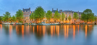 Panoramic view and cityscape of Amsterdam with boats, old buildings and Amstel river, Holland, Netherlands Stock Photography