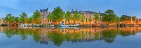 Panoramic view and cityscape of Amsterdam with boats, old buildings and Amstel river, Holland, Netherlands Stock Image