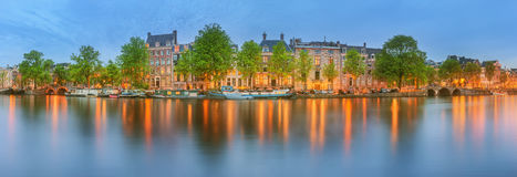 Panoramic view and cityscape of Amsterdam with boats, old buildings and Amstel river, Holland, Netherlands royalty free stock photography