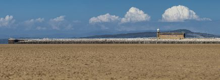 Lighthouse on Pier of Morecambe Bay. Panoramic view of coast of Morecambe in United Kingdom at low tide Stock Images