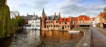 Panoramic view of the colorful buildings of Bruges Belgium reflecting on the canal water stock photos
