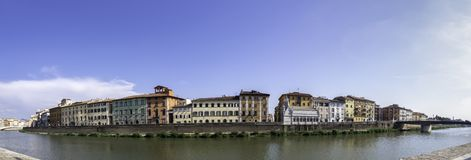 Panoramic view of the colorful houses on the banks of the Arno river from the other shore, Pisa royalty free stock photo