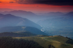 Panoramic view of colorful sunset in the mountains. Dramatic overcast sky. Royalty Free Stock Images