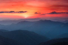 Panoramic view of colorful sunset in the mountains. Dramatic overcast sky. Royalty Free Stock Photo