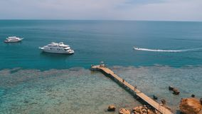 Panoramic view on Coral Beach with Pier and Pleasure Boat on Red Sea at Reef. Egypt. stock video
