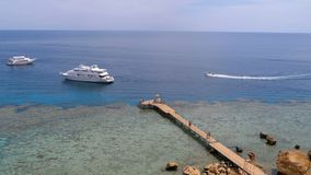 Panoramic view on Coral Beach with Pier and Pleasure Boat on Red Sea at Reef. Egypt. stock video footage