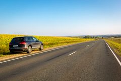 Black car parked on road side with field of golden sunflower background . royalty free stock images