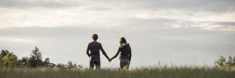 Panoramic view on couple holding hands in field Royalty Free Stock Images