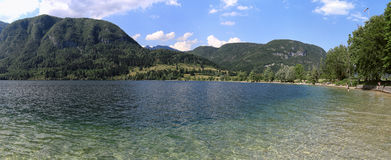 Panoramic view of the crystal clear waters of lake Bohinj a famous destination not far from lake Bled, in Slovenia. Royalty Free Stock Images