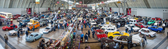 Panoramic view on a different cars and bikes in the exhibition hall. Royalty Free Stock Photography