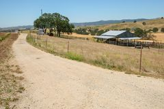Panoramic view of a dirt road passing next to a ranch in California. CALIFORNIA, USA - JUNE 10, 2006. A dirt road passes next to a typical ranch in this region stock photo
