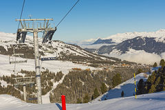 Panoramic view down an alpine mountain valley. Panoramic view down snow covered valley in alpine mountain range with conifer pine trees and ski lift Royalty Free Stock Photos