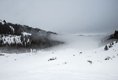 Panoramic view down a mountain valley with low clouds and overca Royalty Free Stock Photography