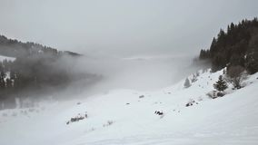 Panoramic view down a mountain valley with low clouds and overcast sky. Panoramic view of a snow covered mountain range looking down valley with low clouds and stock video