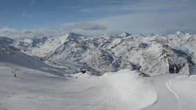 Panoramic view down a mountain valley range with ski piste stock video