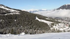 Panoramic view down a mountain valley range with ski resort village stock video footage