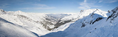 Panoramic view down a  snowy mountain valley Royalty Free Stock Images