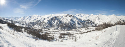 Panoramic view down a  snowy mountain valley Stock Image