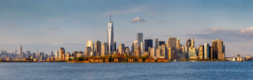 Panoramic view of Downtown Manhattan and New York skyscrapers. Warm late afternoon light illuminating Lower Manhattan. Panoramic view spanning from Brooklyn Royalty Free Stock Image