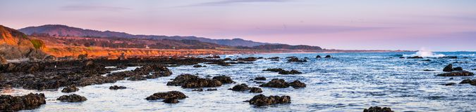 Panoramic view of the dramatic Pacific Ocean coastline at sunset, during low tide, Santa Cruz mountains in the background; San. Francisco bay area, California stock photo