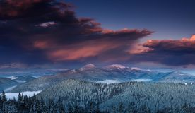 Panoramic view of dramatic sunset in the winter mountains. Wooded hills covered with snow, fog rising from valleys, colorful cloudy sky - this is impressive Stock Photography
