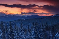 Panoramic view of dramatic sunset in the winter mountains. Wooded hills covered with snow, fog rising from valleys, colorful cloudy sky - this is impressive Royalty Free Stock Image