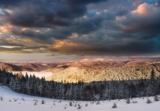 Panoramic view of dramatic sunset in the winter mountains. Wooded hills covered with snow, fog rising from valleys, colorful cloudy sky - this is impressive Stock Image