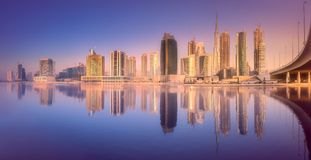 Dubai Business bay during purple sunrise. Panoramic view of Dubai Business bay with reflection of skyscrapers on water during purple sunrise, UAE Stock Photos