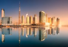 Panoramic view of Dubai Business bay, UAE. Panoramic view of Dubai Business bay with reflection of skyscrapers on water during sunrise, UAE Royalty Free Stock Photos