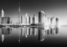Panoramic view of Dubai Business bay, UAE. Panoramic view of Dubai Business bay with reflection of skyscrapers on water during sunrise, UAE . Black and white Stock Image