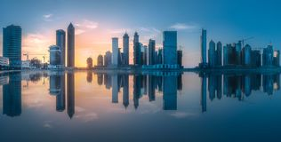 Panoramic view of Dubai Business bay, UAE. Panoramic view of Dubai Business bay with reflection of skyscrapers on water during sunrise, UAE royalty free stock image