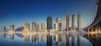 Panoramic view of Dubai Business bay, UAE. Panoramic view of Dubai Business bay with reflection of skyscrapers on water during sunrise, UAE royalty free stock photography