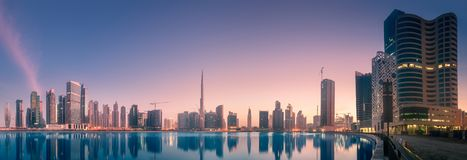 Panoramic view of Dubai Business bay, UAE. Panoramic view of Dubai Business bay with reflection of skyscrapers on water during sunrise, UAE. Clipping path of sky royalty free stock photos