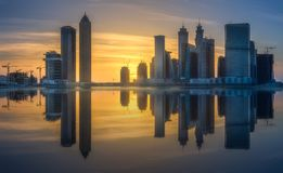 Panoramic view of Dubai Business bay, UAE. Vibrant panoramic view of Dubai Business bay at evening light with and reflection of buildings on water, UAE royalty free stock images