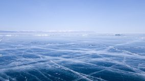 Panoramic view of the endless ice of lake Baikal in winter. Deep cracks on the surface of bright blue ice. Sunny clear weather stock photography