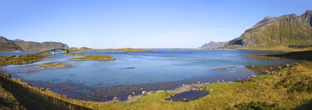 Panoramic view from fredvang bridges to ramberg in autumn with mountains in backgrond and beautiful blue fjord in foreground , lof. Panoramic view from famous Royalty Free Stock Images