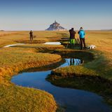 Panoramic view of famous historic Le Mont Saint-Michel tidal island on a sunny day with blue sky and clouds in summer, Normandy. stock photo