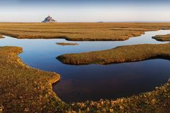 Panoramic view of famous historic Le Mont Saint-Michel tidal island on a sunny day with blue sky and clouds in summer, Normandy. stock images
