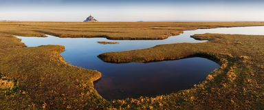 Panoramic view of famous historic Le Mont Saint-Michel tidal island on a sunny day with blue sky and clouds in summer, Normandy. royalty free stock images