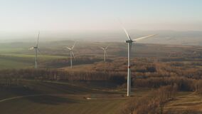 Panoramic view of a farm with wind turbine at sunset. Wind power turbines generating electricity.